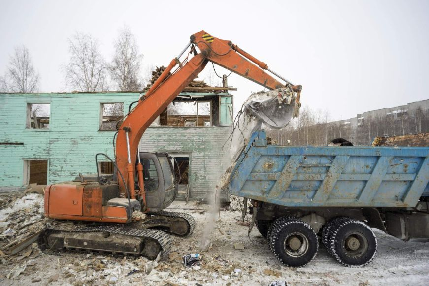 Excavator loading up a truck with commercial demolition waste