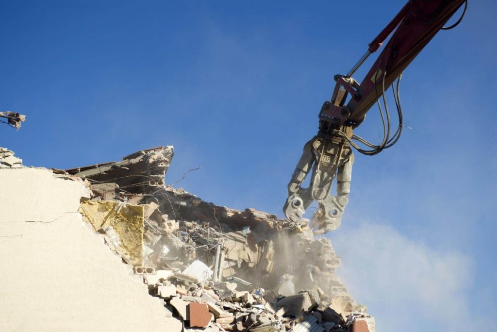 Giant cutting machine chopping up a demolishing a building before excavating can start