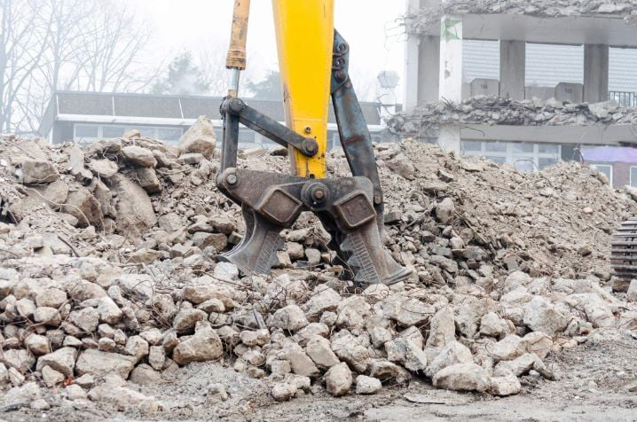 Massive crusher chopping up concrete in smaller chunks for transportation on an industrial site
