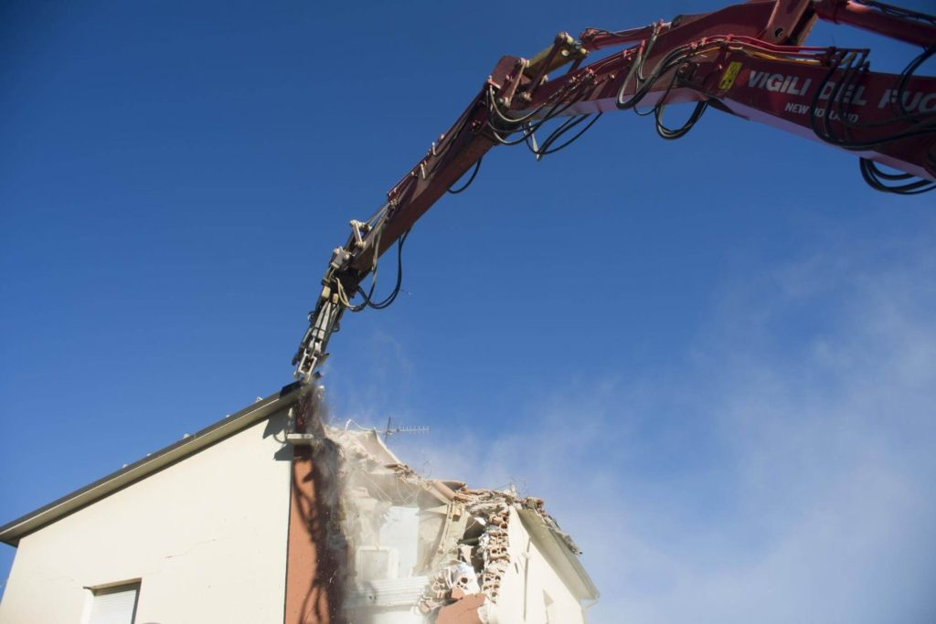 Large machine cutting up a house on a residential demolition site