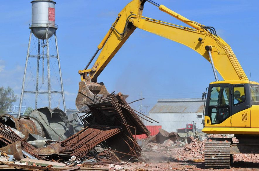Excavator moving industrial demolition waste for recycling pickup