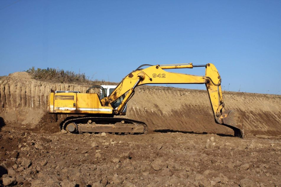 Excavator levelling an industrial excavation site