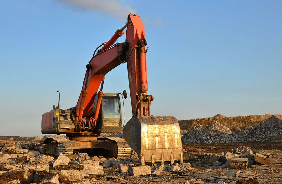 Large excavator organising residential demolition waste on a recycling site